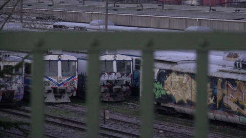 Graffiti trains viewed through fence Footage