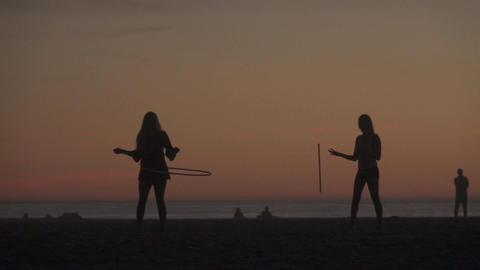 Silhouettes Practice Circus Tricks on Beach Footage