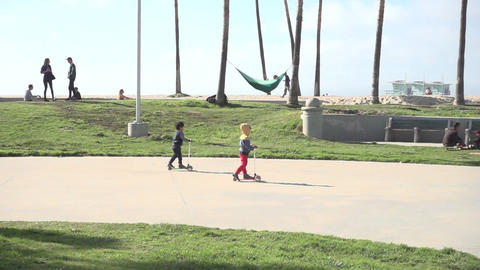 Children ride scooters through a park near the beach Footage