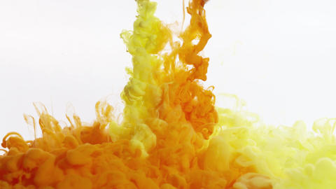 Clouds of yellow and orange ink expand downward in clear liquid, filling frame Footage