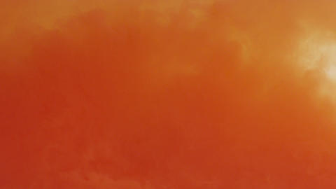 An orange to yellow gradient of ink flows through water in slow motion Footage