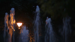 Artesian fountain with several threads of water that goes during the night, lit  Live Action