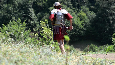 Roman soldier running on a downhill slope to hide in the woods 64 Footage