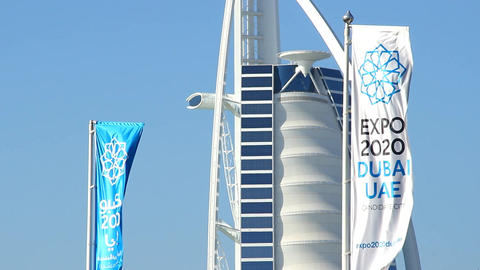 Blue and white banner about Expo 2020 flutter on wind against Burj Al Arab hotel Footage