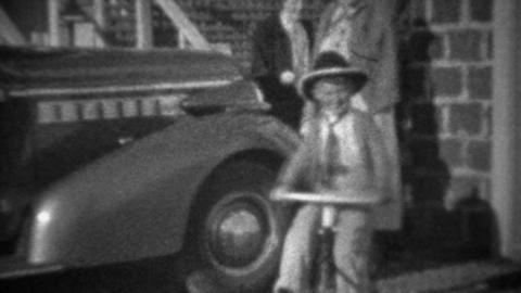 1946: Boy riding bike past family car and cute waving to camera Footage