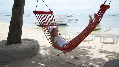child relaxing in a hammock on the sea beach ビデオ