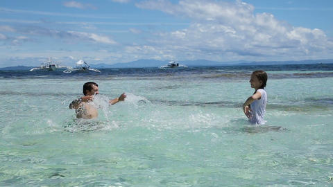 man and his daughter splashing water in the sea Footage