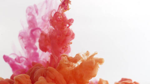 Clouds of pink and orange ink expand in clear liquid, mixing together Footage