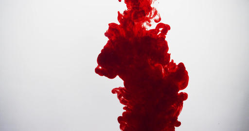 A cloud of red ink from top of frame plumes in clear liquid. Isolated Footage