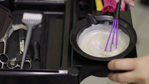 Hairdresser mixing hair dye in bowl in hair salon Footage