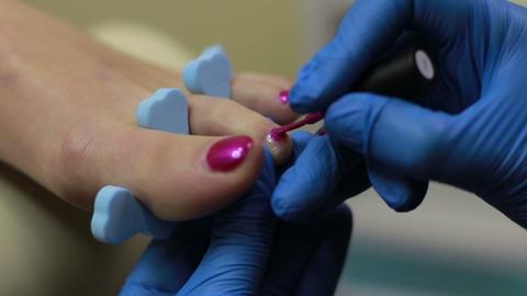 Pedicurist applying nail polish to toenails ビデオ
