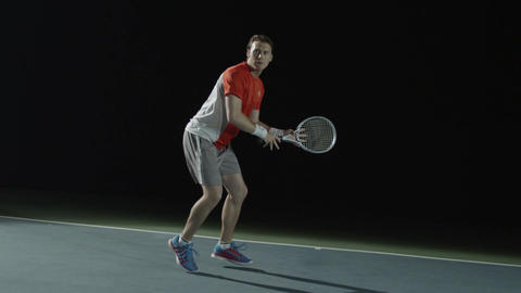 A male tennis player practices on a court at nighttime Footage