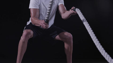 Tilt up to a closeup of a man's face working out with Battle Ropes Footage
