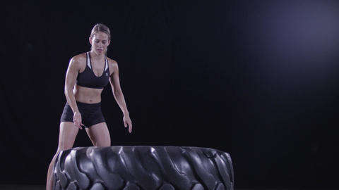Athletic Blonde Woman Lifts Giant Tire in Slow Motion Footage