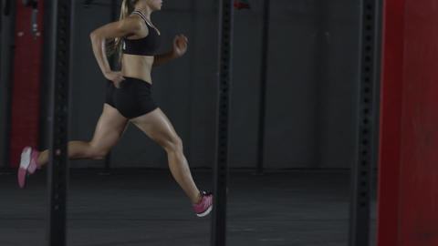 Slow motion tracking shot of blonde in athletic gear doing wind sprints Footage