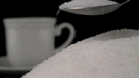 Spoonful of white sugar added in cup of coffee on black Footage