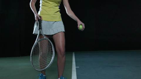 A woman bounces a ball on a tennis court in slow motion before serving Footage