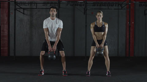 A man and woman doing kettle bell exercising and lifts, squats Live Action