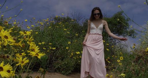 Woman Walks Forward on Flower Path Footage