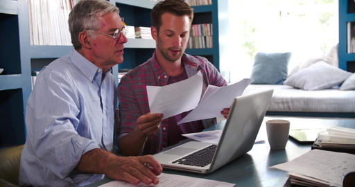Son Helping Senior Parent With Paperwork In Home Office Footage
