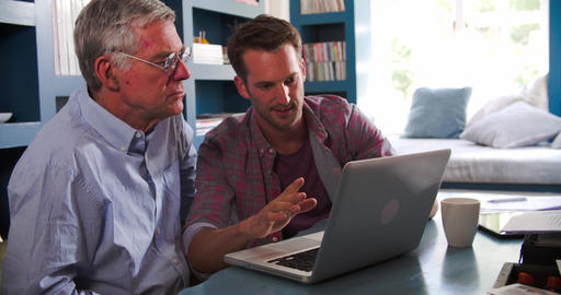 Son Helping Senior Parent With Computer In Home Office Footage