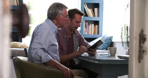 Son Helping Senior Father With Digital Tablet At Home Live Action