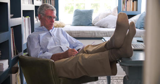 Senior Man In Home Office Doing Paperwork With Feet On Desk Footage