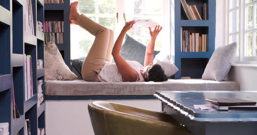 Mature Woman Lying On Couch At Home Reading Book Footage