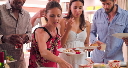 Group Of Friends Choosing Food From Party Buffet At Home Live Action