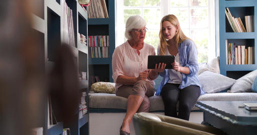 Daughter Helping Senior Mother With Digital Tablet At Home Live Action