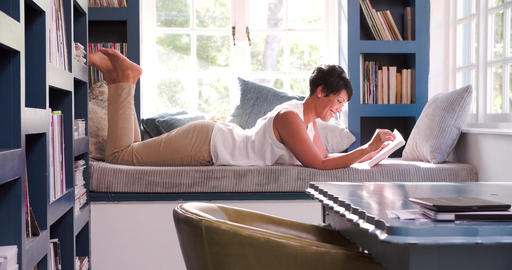 Mature Woman Lying On Couch At Home Reading Book Live Action