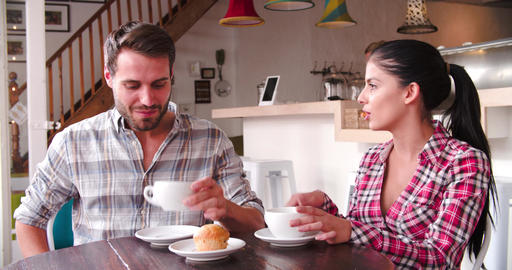 Young adult couple talking at a table in a cafe Live Action