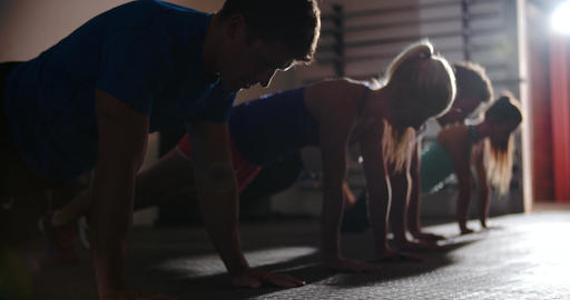 Four people doing press ups at a gym Footage