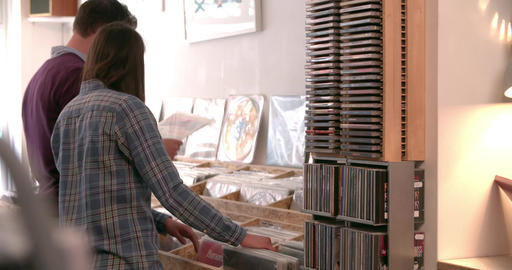 Two people browsing through records at a record shop Live Action