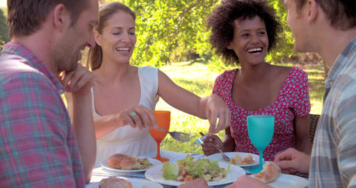 Four friends eating at a table together outdoors Footage