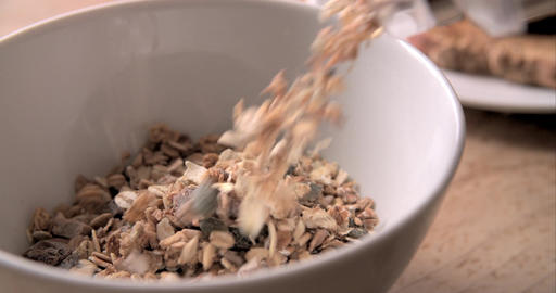 Slow Motion Shot Of Pouring Muesli Into Bowl Footage