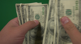 Hundred-dollar bills in hands on green background Footage