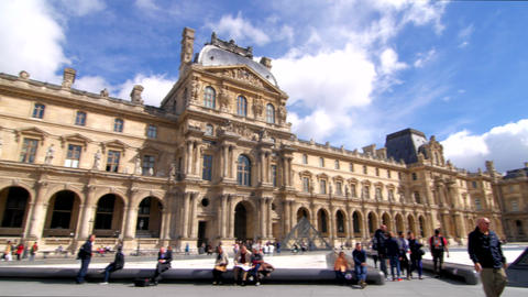 Louvre Building With Tourists Walking And Blue Sky Pan stock footage