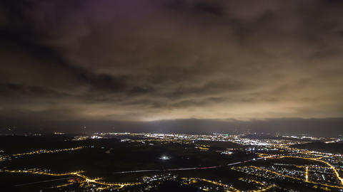 Time lapse of big clouds moving quickly over the city in the night Footage