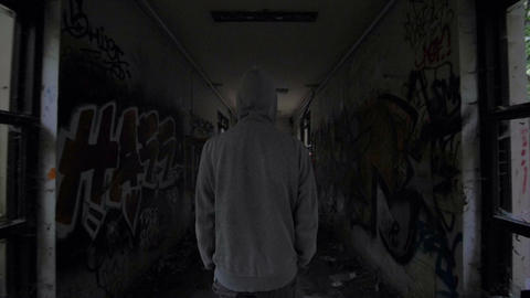 Slow motion of a guy with hood walking through abandoned building Footage