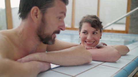 Young couple relaxing in the swimming pool close up Footage