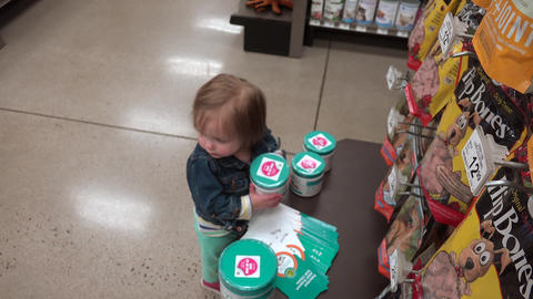 Toddler unstacking plastic jars at pet store practicing spatial learning Footage