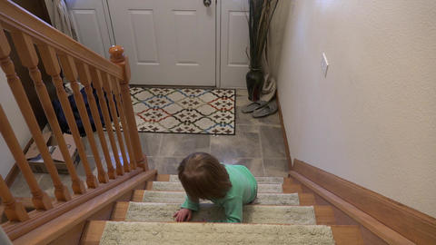 Toddler crawling down staircase backwards to front door Footage