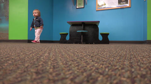 Toddler walking from kids table across carpet floor to camera Footage