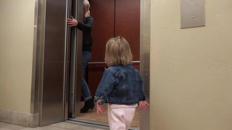 Mom holding elevator door for toddler entering hospital hallway Footage