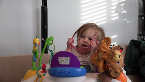 Toddler takes off rose colored glasses on toddler in baby einstein office Live Action