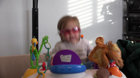 Toddler bouncing in seated toy with rose colored glasses in baby einstein Footage