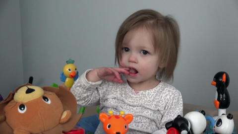 Toddler soothing teething pain with fingers in mouth on toy setup Live Action