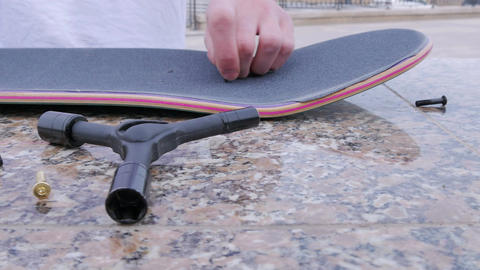 Guy makes bolt holes in the skateboard Footage