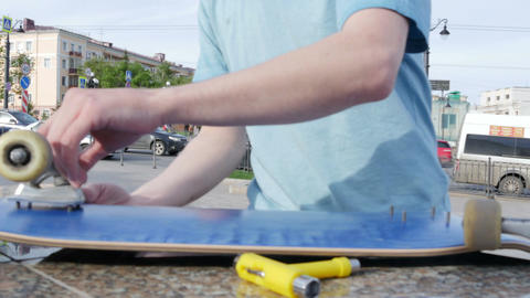 Guy puts the wheels to the skateboard and starts to twist bolts Footage